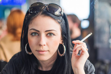 Young beautiful woman sitting in street cafe smokes a cigarette, looking to camera, background blur, head and shoulders