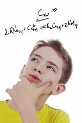 enfant garçon jeune réfélchissant à une formule chimique