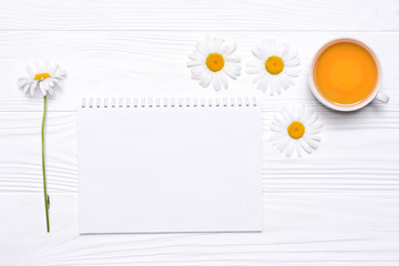 Chamomile flowers, notebook with place for text, cup with tea on white wooden background. View from above