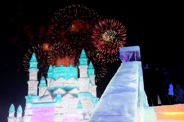 Fireworks light up the sky behind ice sculptures during the opening of the annual ice festival in Harbin, Heilongjiang province
