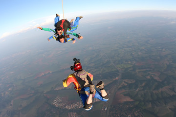 Professional parachutist taking photos of a tandem jump