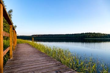 ein See mit Holzsteg umgeben von Wald
