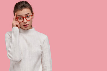 Concerned attractive woman keeps index finger on temple, has tired look, finds solution, wears glasses, models against pink studio wall with copy space for your promotional content. Horizontal shot