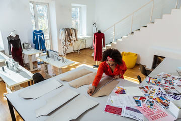 Concentrated curly African American designer using measuring tape