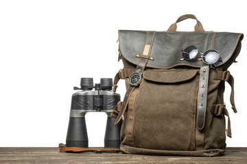Vintage brown backpack with tourism accessories on a table with an isolated background.