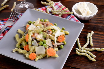 Spinach pasta with spinach and gorgonzola dressing with peas and carrots