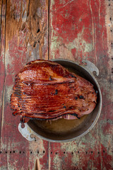 Spiral-cut baked glazed ham on rustic painted table flat lay