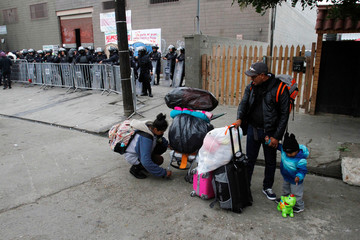 Migrants leave a temporary shelter voluntarily in Tijuana