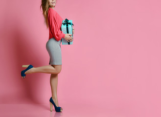 Woman walking with shopping presents gift box for happy valentines day on pink