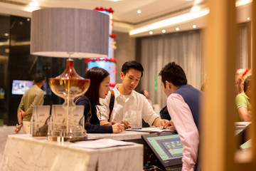 Asian couple checking in at counter with reception at hotel.