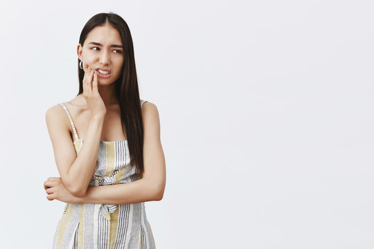 Boyfriend fouond out about scratch on car. Nervous troubled attractive and fashionable female model in matching outfit, holding palm on jaw, staring right anxiously, thinking about what she did