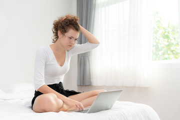 Young woman sitting on the bed in the bedroom with her laptop has a problem