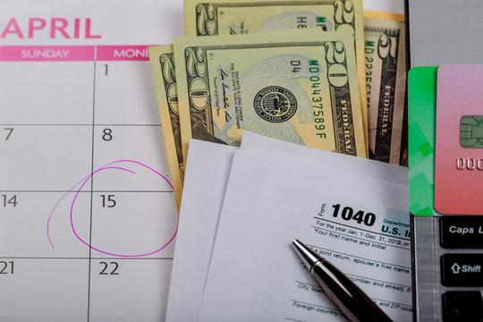 Tax time Closeup of U.S. 1040 tax return with U S dollars bills and for April Calendar