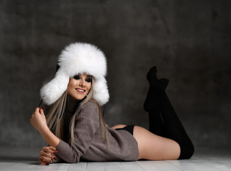 Portrait of young beautiful woman in blue white fashion arctic fox winter fur ear flaps hat