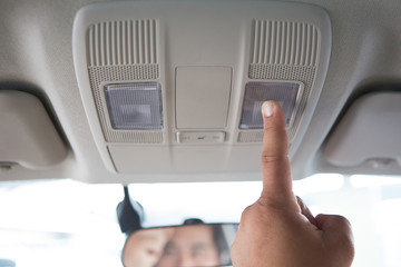 Men's hand pressing the car's ceiling light
