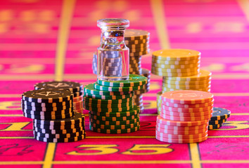 Casino table. American Roulette layout. Dolly is standing on stacks of playing chips.