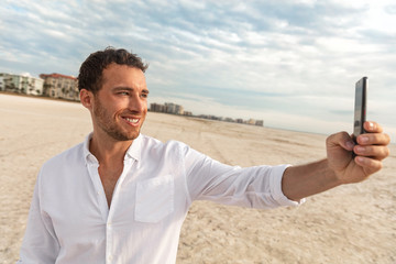 Selfie vacation beach man in white linen shirt taking photo with mobile phone on honeymoon travel vacation. Happy young using smartphone on holdiay.