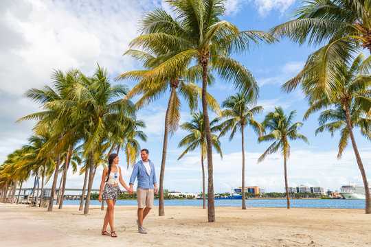 Miami people lifestyle - couple walking holding hands talking enjoying walk on beach with palm trees. Florida travel destination.