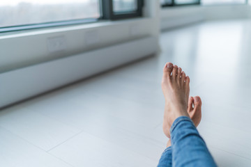 Home relax comfort lifestyle woman barefoot relaxing at warm radiators heat system in apartment or condo living. Cozy winter electric baseboards in house. Closeup of feet.
