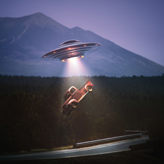 Unidentified flying object lifting a car from road. Concept of alien abduction. Clipping path included.