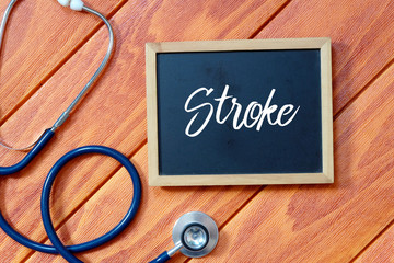 Top view of stethoscope and blackboard written with Stroke on wooden background. Health concept.