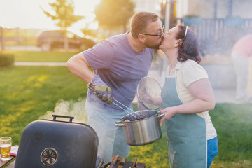Picture of middle age couple making barbeque and kissing in their backyard. Family lunch on summer day.