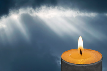 Burning candle on a background of sunlight breaks through the clouds