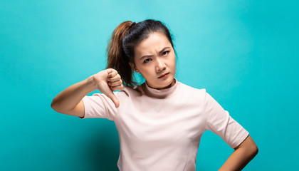 Portrait of angry woman standing on blue background