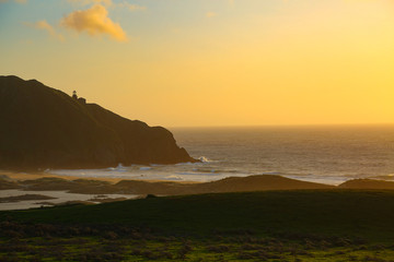 Sunsets over the california coast with a lighthouse on a point.
