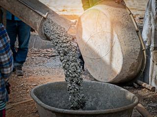 concrete mixer truck pouring concrete into large basin