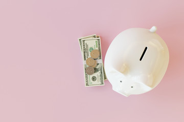 White piggy bank with coins and dollar banknotes on pink background. 3d rendering