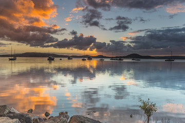 Sunrise and Cloud Reflections on the Bay with Boats