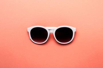 Women's sunglasses in white rim on living coral background Wall mural