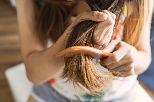 Woman combing tangled hair, Hair problems concept