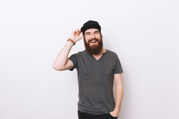 Portrait o happy bearded man with hand in pocket and hold his hat