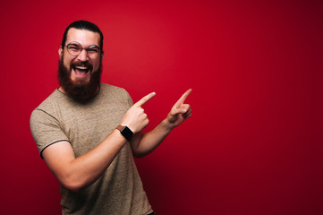 Portrait of screaming bearded boy, pointing to copy space in right