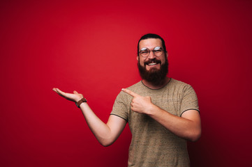 Portrait of smiling bearded boy, pointing to copy space, over red background