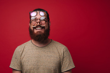 Photo of funny bearded man with many glasses on face