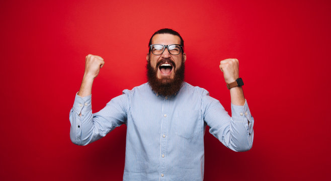Portrait of screaming man, celebrating his victory and gesturing with fists up