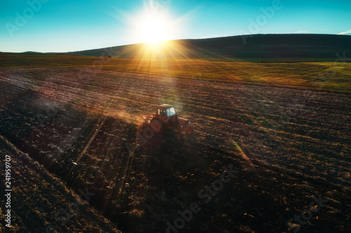 Wall mural Aerial view of tractor cultivating field at spring