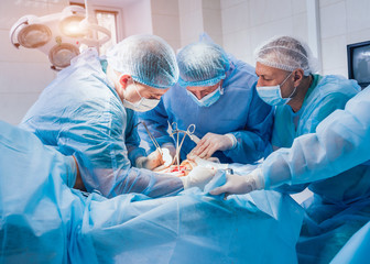 Process of trauma surgery operation. Group of surgeons in operating room with surgery equipment.