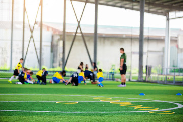 equipment on green artificial turf with blurry kid players training background