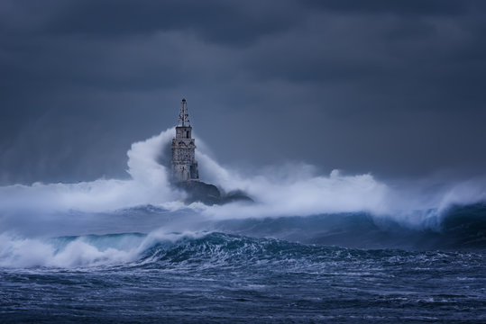 Big wave against old Lighthouse in the port of Ahtopol, Black Sea, Bulgaria on a moody stormy day. Danger, dramatic scene.
