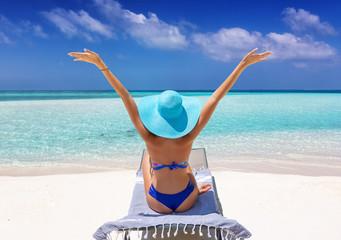 Glückliche Frau im Bikini genießt ihren Urlaub am tropischen Traumstrand mit blauem Himmel und türkisem Meer
