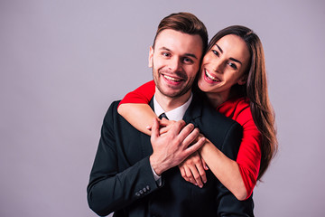 Love you so much! Beautiful stylish and elegant couple in suit and dress are hugging, have a fun and posing isolated in studio. Holidays and events. St Valentine's day. Day of lovers