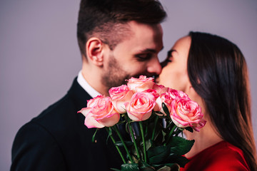 Close up photo of beautiful young romantic couple while they kissing behind the bouquet of roses in hands. St Valentine's day.