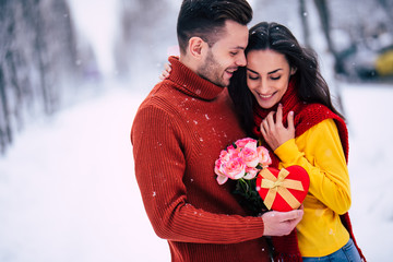 Celebration of St Valentine's day. Happy and beautiful young couple in love are walking together outdoors in winter city park and hugging and kissing each other. Gifts and flowers