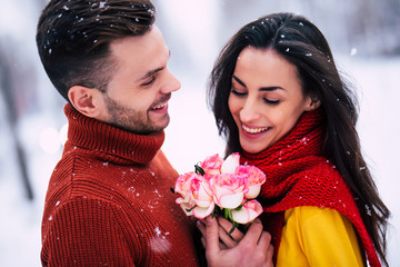 With big love. Close up photo of beautiful happy couple outdoors. Handsome man is giving flowers to cute woman
