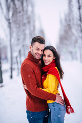 Beautiful happy young couple in love are hugging in sweaters outdoors on the winter city background. Holidays. St Valentines day