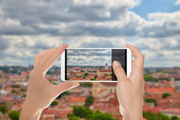 A man is making a photo of historical part of the city of Vilnius on a mobile phone.
